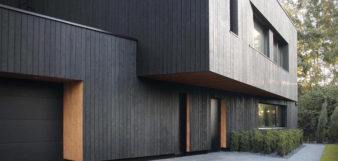 Czarna i minimalistyczna forma domu z elewacjami z drewna opalanego tradycyjną japońską techniką